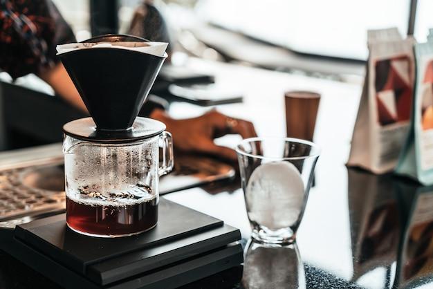 Goteo frío café arábica negro en vaso con bola de hielo
