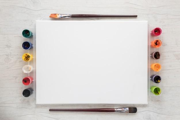 Gouache y pinceles cerca de papel blanco.