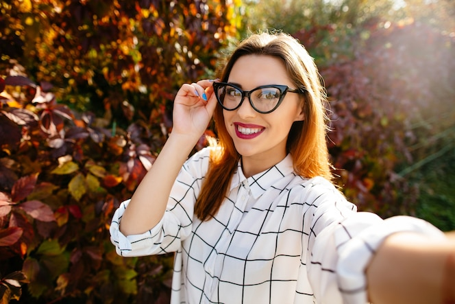 Gougeus modelo toma selfie mientras sostiene sus gafas con una mano en el jardín de otoño.