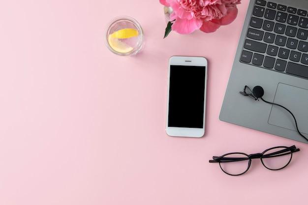 Grabación de podcast, micrófono, computadora portátil, teléfono, agua con limón y vasos en plano rosa