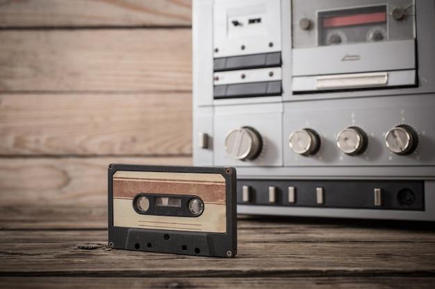 Grabadora de cinta antigua y cassette sobre mesa de madera