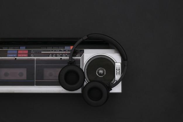 Grabadora de cinta de audio boombox y auriculares estéreo sobre fondo negro. retro de los 80. vista superior. endecha plana