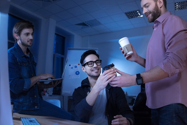 Gracias. hombre agradable alegre feliz sonriendo y tomando café mientras disfruta de su descanso con colegas