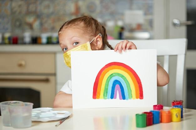 Gracias a nhs. niño con máscara protectora pintando el arcoíris durante la cuarentena de covid-19 en casa. brote de coronavirus covid-19.