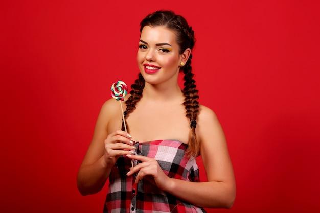 Graciosa joven sosteniendo una piruleta y posando para kamerñ ‹sobre pared roja, pared roja, coletas