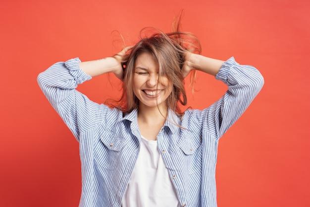 Graciosa, linda chica divirtiéndose mientras juega con el pelo aislado en una pared roja