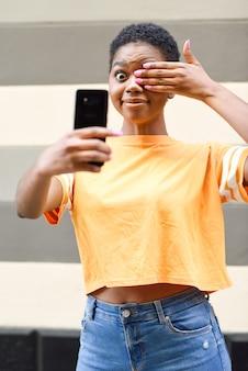 Graciosa mujer negra tomando fotografías selfie con expresión feliz al aire libre