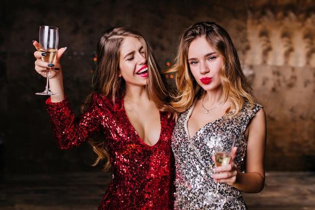 Graciosa mujer de pelo largo cantando con los ojos cerrados y levantando una copa de champán