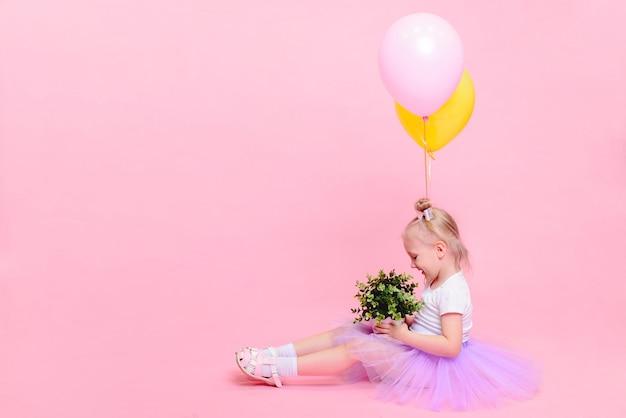 Graciosa niña en camiseta blanca y falda lila con globos sobre fondo rosa. retrato infantil con espacio para texto.