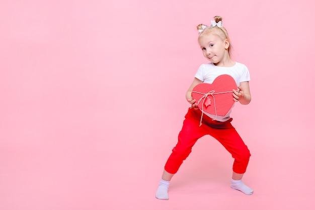Graciosa niña en una camiseta blanca y pantalón rojo con una caja en forma de corazón sobre un fondo rosa. retrato infantil con espacio para texto.