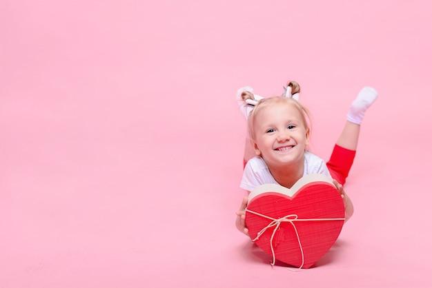 Graciosa niña en una camiseta blanca y pantalón rojo con una caja en forma de corazón sobre un fondo rosa.