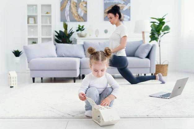 Graciosa niña jugando en casa mientras su madre haciendo fitness