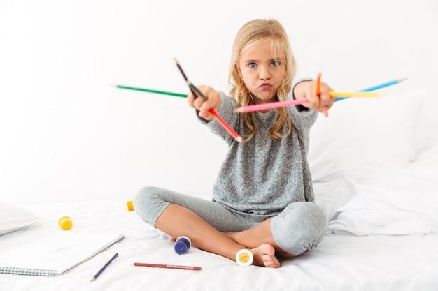 Graciosa niña en pijama gris jugando con lápices de colores, sentado en la cama