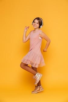 Graciosa niña sonriente en auriculares bailando aislado sobre amarillo