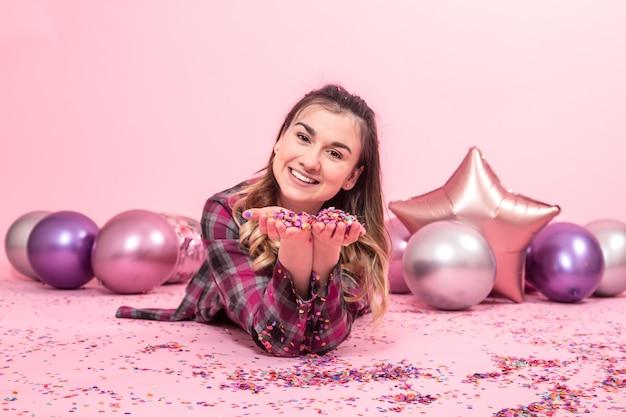 Graciosa sopla confeti en sus manos. globos de colores en una pared rosa