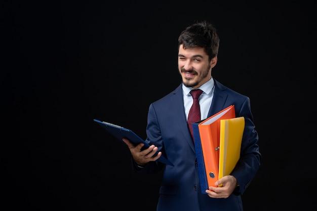 Gracioso adulto emocional en traje sosteniendo varios documentos en la pared oscura aislada