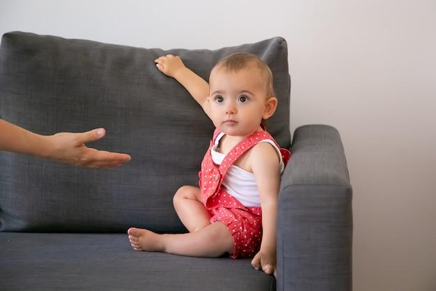 Gracioso bebé sentado en un sofá gris y mirando a una persona irreconocible. alguien dando la mano a la adorable niña en pantalones cortos de peto rojo. familia, infancia y concepto de hogar.