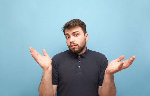 Gracioso hombre barbudo con una camiseta oscura muestra una confusión en azul