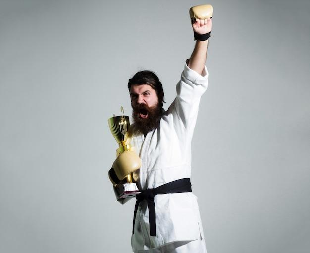 Gracioso karate hombre caucásico hipster en kimono blanco con cinturón negro y guantes de boxeo con cara feliz gritando sostiene copa de campeón de oro, aislado en gris