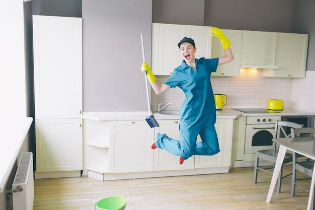 Gracioso limpiador salta en la cocina