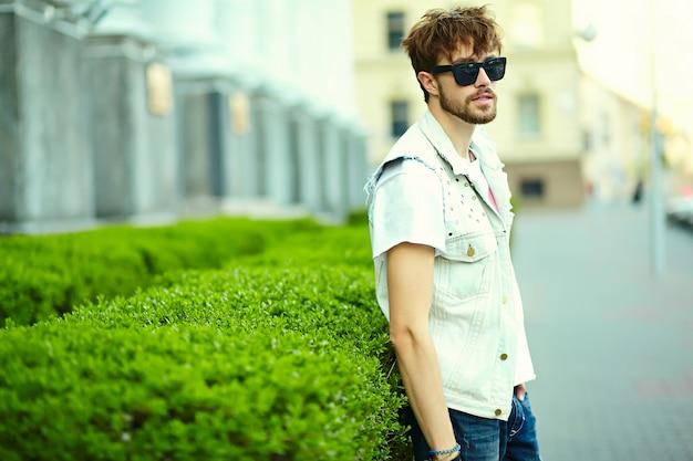 Gracioso sonriente hipster hombre guapo en elegante ropa de verano en la calle con gafas de sol