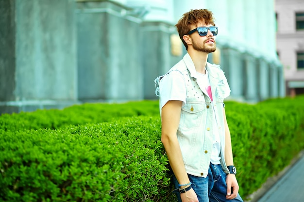 Gracioso sonriente hipster hombre guapo en elegante ropa de verano en la calle posando cerca de la ciudad verde