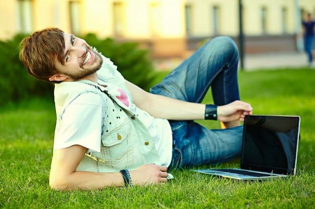 Gracioso sonriente hipster hombre guapo en elegante ropa de verano en la calle sentado en el césped en el parque con notebook