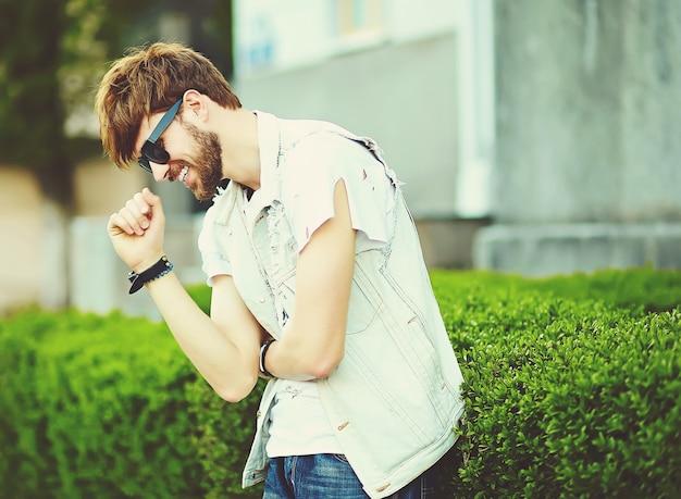 Gracioso sonriente hipster hombre guapo en elegante tela en la calle con gafas de sol