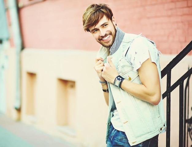 Gracioso sonriente hipster hombre guapo en ropa de verano elegante posando en la calle