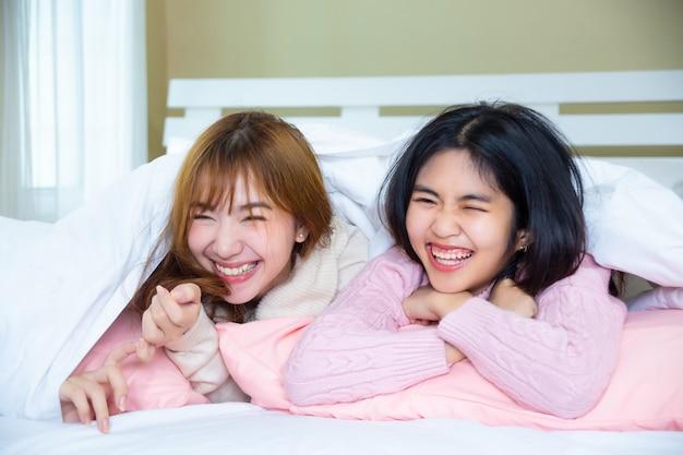 Graciosos amigos acostado debajo de la manta con almohadas en la cama