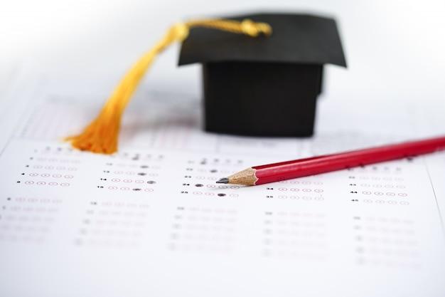 Graduación brecha sombrero y lápiz sobre fondo de hoja de respuesta