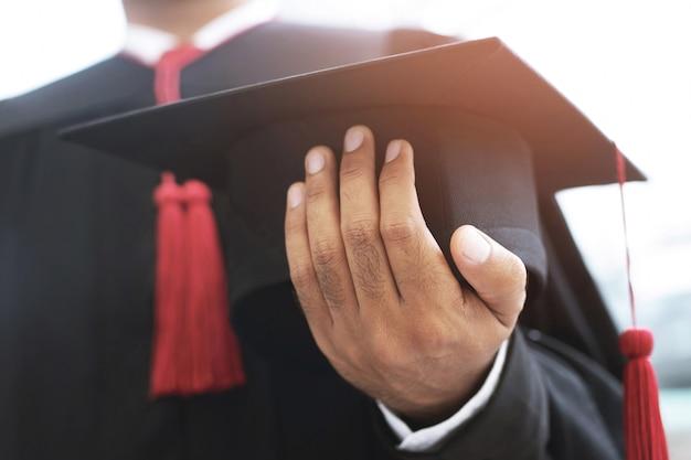 Graduación, el estudiante tiene sombreros en la mano durante el comienzo de los graduados de éxito de la universidad