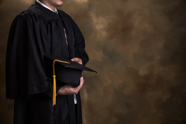Graduación, el estudiante tiene sombreros en la mano durante los graduados de éxito inicial