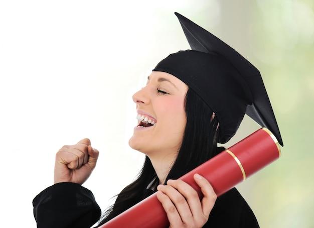 Graduación de gloria y orgullo, mujer feliz con diploma en las manos