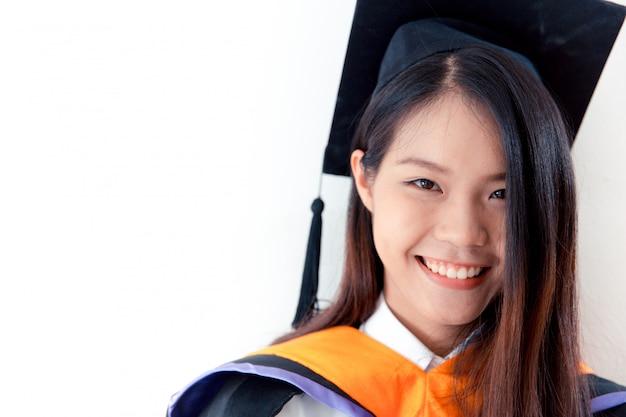 Graduación linda asiática del retrato de las mujeres aislada en blanco, universidad de tailandia.