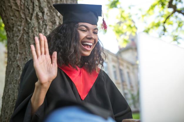 Graduación. una niña en toga académica sentada bajo el árbol con una computadora portátil