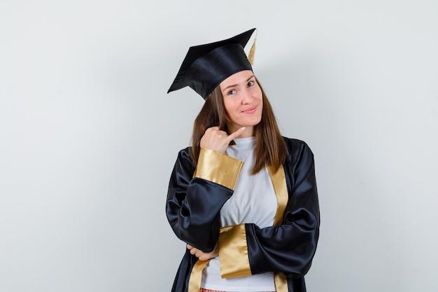 Graduada femenina apuntando a la esquina superior derecha en uniforme, ropa casual y luciendo esperanzada, vista frontal.