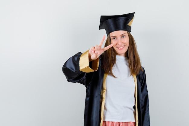 Graduada femenina mostrando gesto de victoria en uniforme, ropa casual y mirando confiado, vista frontal.