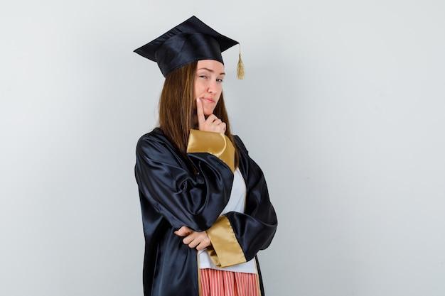 Graduada femenina de pie en pose de pensamiento en uniforme, ropa casual y con un aspecto sensible, vista frontal.