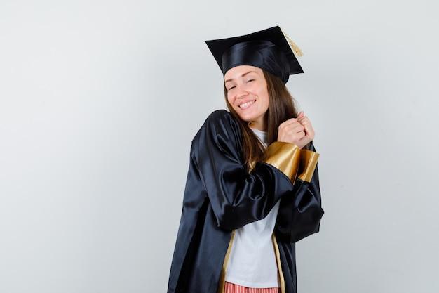 Graduada femenina posando con las manos juntas en uniforme, ropa casual y mirando alegre, vista frontal.