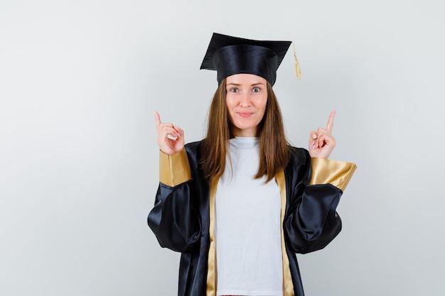 Graduada femenina en uniforme, ropa casual apuntando hacia arriba y mirando alegre, vista frontal.