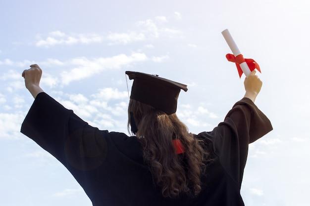 Graduada, levanta las manos y celebra con certificado.