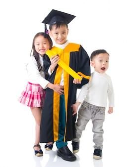 Graduado asiático del niño de la escuela en vestido y casquillo de la graduación. tomando foto con hermana y hermano.