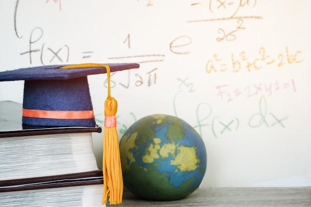 Graduado de educación birrete azul sombrero en libro de texto con fórmula ecuación matemáticas