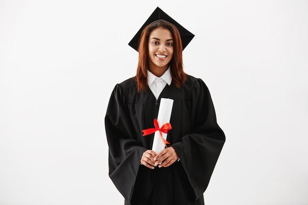 Graduado femenino africano que sonríe sosteniendo el diploma.