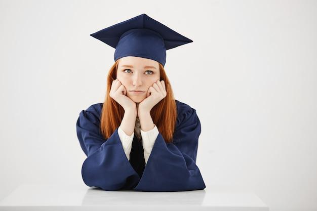 Graduado femenino cansado aburrido que piensa sentarse sobre el backround blanco.
