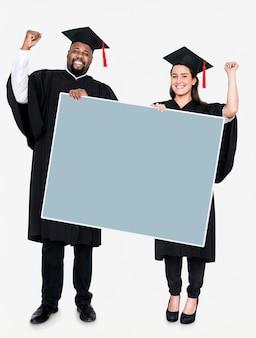 Graduado femenino y masculino que lleva a cabo un espacio de la copia