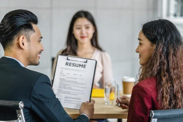 Graduado de la mujer asiática joven que se entrevista con dos gerente cuando se discute
