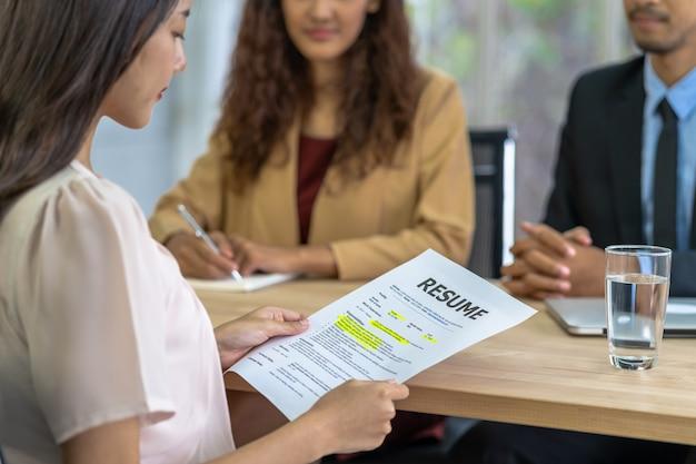 Graduado de la mujer asiática joven que sostiene el documento del curriculum vitae y que se prepara para dos gerentes