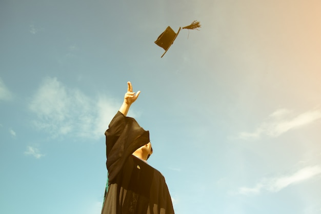 Un graduado tiró un sombrero hasta el cielo de la ceremonia de graduación en el día de graduación